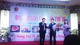 Nguyễn Thế Anh (trái) trong một buổi đại hội chi trả hoa hồng cho nhà đầu tư