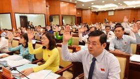Các đại biểu HĐND TPHCM biểu quyết thông qua chương trình kỳ họp. Ảnh: VIỆT DŨNG