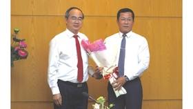 Bí thư Thành ủy TPHCM Nguyễn Thiện Nhân trao quyết định điều động chỉ định Bí thư Quận ủy quận 4 giữ chức Bí thư Quận ủy quận 12. Ảnh: KIỀU PHONG