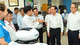 Bí thư Thành ủy TPHCM Nguyễn Văn Nên và đồng chí Nguyễn Thiện Nhân tìm hiểu hoạt động của công ty tại CVPM Quang Trung. Ảnh: VIỆT DŨNG