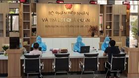 Công chức tại Bộ phận tiếp nhận và trả kết quả hồ sơ UBND quận 11 mặc đồ bảo hộ y tế giải quyết hồ sơ cho người dân trưa ngày 1-7