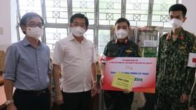 Đồng chí Dương Ngọc Hải tặng quà động viên lực lượng y, bác sĩ làm nhiệm vụ tại một trạm y tế lưu động ở quận Tân Phú. Ảnh: ĐÌNH LÝ