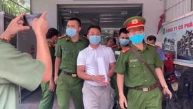 Ông Tùng (áo trắng) bị công an bắt giữ