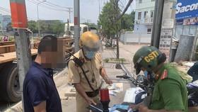 Lực lượng xử phạt một tài xế dừng đỗ ngay tại vòng xoay Phú Hữu. Ảnh: CHÍ THẠCH