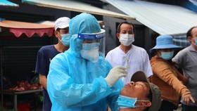Lấy mẫu xét nghiệm Covid-19 của người dân ở quận Bình Tân. Ảnh: CHÍ THẠCH