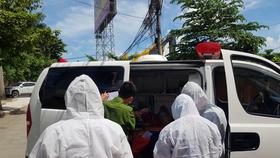 Hai đồng chí hỗ trợ chồng chị Phạm Thị Lý lên xe cấp cứu. Ảnh: BẢO TRÂN