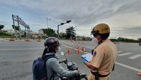 Lực lượng kiểm tra người lưu thông qua chốt ở TP Thủ Đức. Ảnh: CHÍ THẠCH