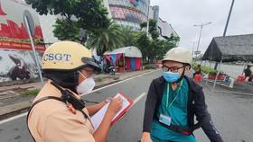 Lực lượng chức năng kiểm tra người dân tham gia lưu thông trên đường. Ảnh: CHÍ THẠCH