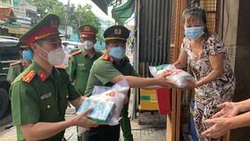 Thượng Tá Trần Anh Thanh, Phó Trưởng Phòng PX03, Công an TPHCM cùng Thượng tá Huỳnh Trung Phong, Trưởng Công an quận 6 gõ cửa nhà dân trao các phần quà hỗ trợ. Ảnh: CHÍ THẠCH