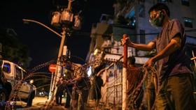 Lực lượng tháo gỡ rào chắn bằng khung sắt, dây kẽm thép gai ở giao lộ đườngTrần Minh Quyền – Điện Biên Phủ, phường 11, quận 10, TPHCM tối 29-9. Ảnh: DŨNG PHƯƠNG