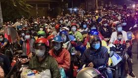 Hàng ngàn người dân ùn ứ về quê bằng xe máy sau khi TP nới lỏng giãn cách ở cửa ngõ về miền Tây. Ảnh: C.T