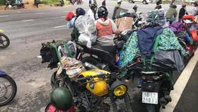 Gần 100 người đi xe máy chở theo hành lý, đồ đạc về quê được vận động ở lại TPHCM. Ảnh: C.T