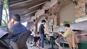 Nhiều khách ngồi tại bàn thoải mái uống cà phê nói chuyện không đeo khẩu trang. Ảnh: C.T