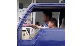 Thiếu niên hướng dẫn em bé 8 tuổi điều khiển xe tải (ảnh cắt từ clip)