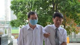 Khoảng 7 giờ, ông Vũ Huy Hoàng được luật sư đưa tới tòa. Ảnh: ĐỖ TRUNG