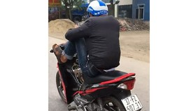 Nam thanh niên vừa dùng điện thoại vừa chạy xe bằng 2 chân. Ảnh cắt từ clip