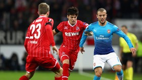 Jack Wilshere (phải, Arsenal) kiểm soát bóng trước Jorge Mere (Cologne). Ảnh: Getty Images.