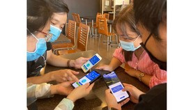 Young people are helping one another to install Bluezone app on their smart devices. (Photo: SGGP)