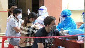 Wesly (in black T-shirt, from Canada) is having his health checked after being vaccinated. (Photo: SGGP)