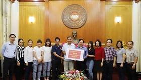 Huấn luyện viên Trưởng đội tuyển bóng đá nữ Việt Nam Mai Đức Chung trao số tiền ủng hộ cho UBTW MTTQ Việt Nam
