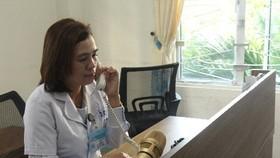 Bác sĩ Phan Thị Thanh Thủy đang tư vấn cho một người dân về cách phòng chống Covid-19 tại bàn trực