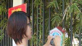 Cô giáo Nguyễn Thị Bích Trâm, trường Tiểu học Tây Hồ bỏ pin vào ngôi nhà được treo trước hàng rào của trường