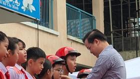 Thầy Trần Nguyễn Minh Thành trao tặng mũ bảo hiểm cho các em học sinh lớp 5 có hoàn cảnh gia đình khó khăn