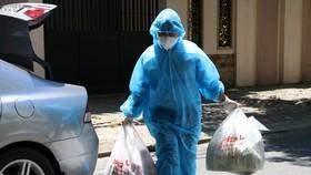 Shipper mặc đồ bảo hộ đi giao hàng cho người dân