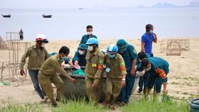 Lực lượng chức năng hỗ trợ ngư dân đưa thuyền thúng lên bờ