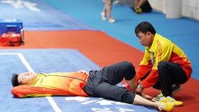 Võ sĩ Trần Xuân Hiệp được bác sĩ chăm sóc. Ảnh: DŨNG PHƯƠNG