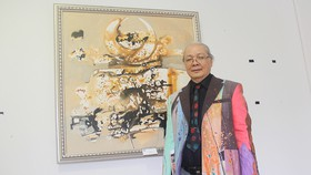 Họa sĩ Uyên Huy bên tác phẩm của mình tại triển lãm