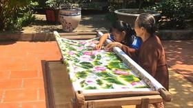 Các bạn trẻ cùng nghệ nhân làng thêu Quất Động bên khung thêu truyền thống