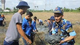 Cán bộ, chiến sĩ Vùng 2 Hải quân tham gia giúp dân đắp đê ngăn mặn