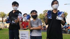 Nhóm học sinh phát khẩu trang vải miễn phí cho người đi đường