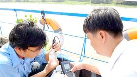 Lực lượng chức năng ở TPHCM kiểm tra chất lượng nước lấy từ sông Sài Gòn đoạn qua huyện Củ Chi. Ảnh: CAO THĂNG