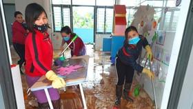 Giáo viên dọn vệ sinh trường lớp sau lũ. Ảnh: DƯƠNG QUANG