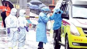 Nhân viên y tế đón bệnh nhân nhiễm Covid-19 tại một bệnh viện ở Daegu, Hàn Quốc. Ảnh: THX