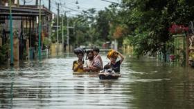 Người dân Indonesia sơ tán khỏi khu vực ngập lụt ở Gresik, Đông Java ngày 15-12-2020. Ảnh: AFP/TTXVN