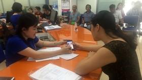 Nhân viên EVN HCM tư vấn cho khách hàng cách tải các ứng dụng để kiểm soát lượng điện tiêu thụ hàng tháng của gia đình mình