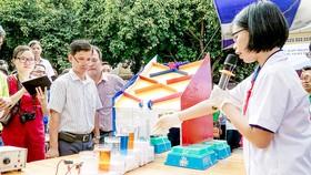 Học sinh Trường THCS Đồng Khởi giới thiệu thí nghiệm phản ứng hóa học theo dạng domino. Ảnh: HOÀNG HÙNG