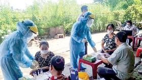 Nhân viên Trung tâm Y tế huyện Bình Chánh lấy mẫu xét nghiệm người dân tại tại chợ Tân Đoàn Việt - Phong Phú vào sáng 2-5. Ảnh: MINH NAM