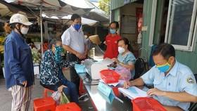 Người đi chợ Bình Thới khai báo y tế trước khi nhận phiếu đi chợ theo thứ tự trong đợt giãn cách vừa qua