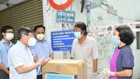 """Chủ tịch UBND TPHCM Nguyễn Thành Phong trao quà hỗ trợ người dân ở """"vùng xanh"""" tại quận Phú Nhuận. Ảnh: VIỆT DŨNG"""