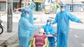 Lấy mẫu xét nghiệm người dân tại đường Trần Nguyên Hãn, quận 8, TPHCM sáng 24-8. Ảnh: CAO THĂNG