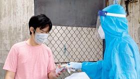 Người dân F0 cư ngụ trên đường 3-2, quận 11, TPHCM nhận thuốc do Quân y phát sau khi được khám sức khỏe và hướng dẫn sử dụng. Ảnh: CAO THĂNG