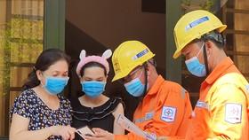 Nhân viên EVNHCMC hướng dẫn người dân sử dụng tiện ích số trong quản lý, tiêu dùng điện