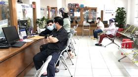 Người dân đến sao y chứng thực, làm giấy tờ tại UBND phường 7, quận Gò Vấp. Ảnh: BÙI TUẤN