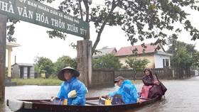 Người dân huyện Quảng Điền, tỉnh Thừa Thiên - Huế  di chuyển trên đường ngập lụt, chiều 17-10. Ảnh: VĂN THẮNG