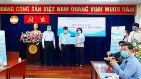 Đại diện Công ty TNHH Phát triển Phú Mỹ Hưng trao bảng tượng trưng ủng hộ 20 tỷ đồng vào Quỹ mua vaccine Covid-19 cho nhân dân TPHCM. Ảnh: HOÀI NAM