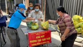 Người dân tại điểm phong tỏa phường 12, quận Tân Bình nhận hàng từ các địa phương hỗ trợ